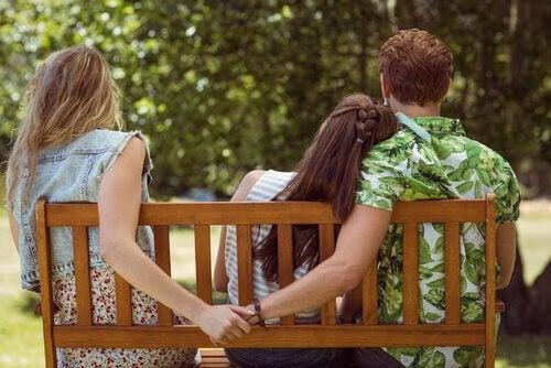 känslomässiga sår från barndomen: man håller om en kvinna och håller en annan kvinnas hand