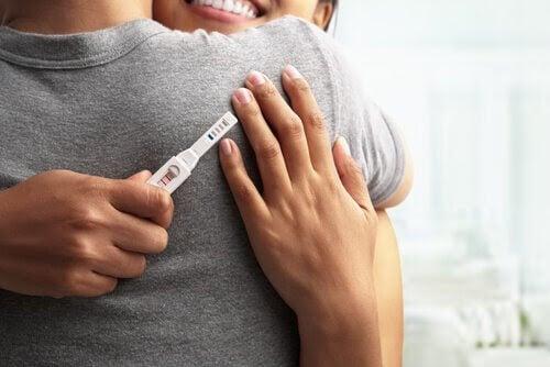 symptomen på en graviditet: kvinna och man kramas och håller i gravtest
