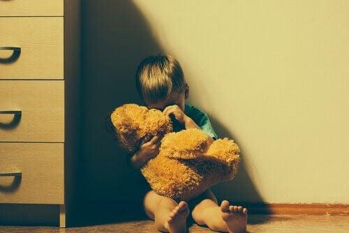 våld i familjen: pojke med nalle sitter i ett hörn
