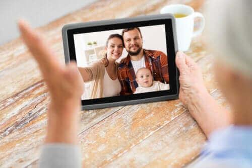 Teknik under coronapandemin: Äldre man har videosamtal med sitt barnbarn