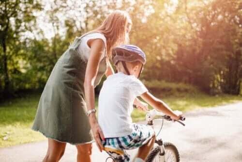 uppmuntrar positivt beteende: mamma hjälper barn cykla