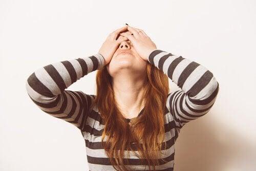symptomen på ägglossning: kvinna håller sig för ögonen