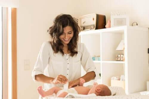 Ditt barns avföring: mamma byter blöja på baby