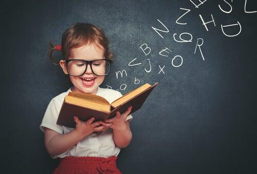 lära sig att läsa: barn med bok framför svart tavla