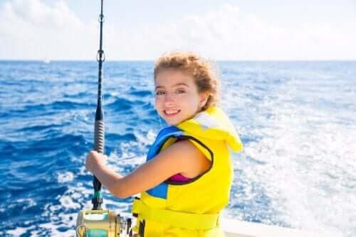 seglar med barn: flicka med fiskespö på båt