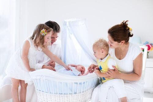 din babys första säng: familj runt baby i vagga
