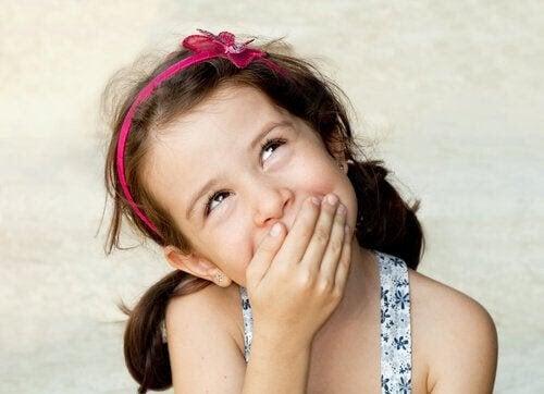 Mytomani hos barn: flicka håller sig för munnen