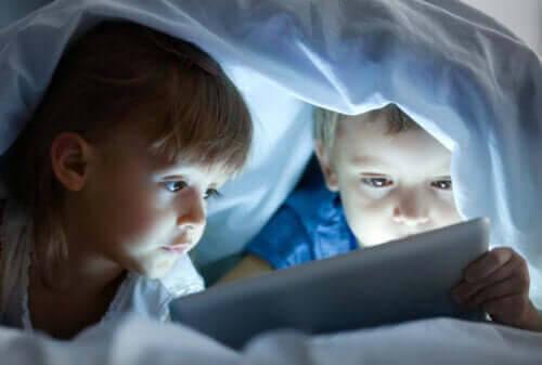 negativa effekterna som skärmtid: barn under täcke med surfplatta
