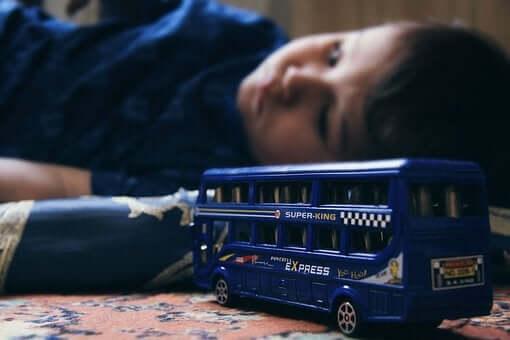 Ett barn med emotionella problem ligger bredvid sin leksaksbil.
