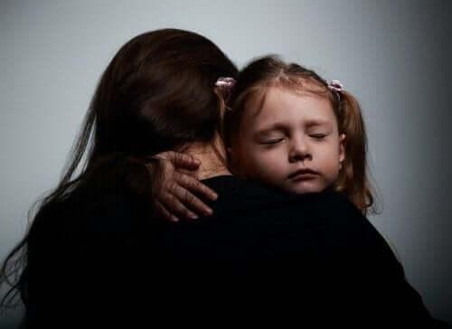 Emotionella problem hos barn: En mamma kramar sitt barn.