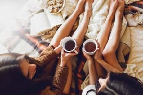 Språket man använder: Två kvinnor pratar med kaffe i handen