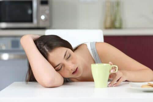 tonåring är utmattad och stressad: tonåring sover mot bord bredvid kaffekopp