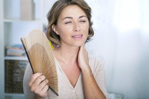 För tidig klimakterium: kvinna fläktar sig med solfjäder