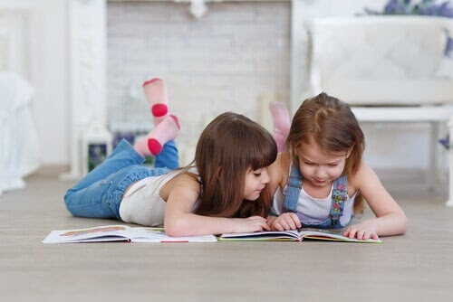 lära barn att hata att läsa: två barn ligger på golvet och tittar i bok