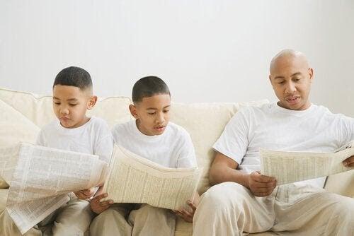 genom modellering: två barn och en pappa läser tidning i soffa