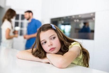 lära barn att vänta: uttråkad flicka väntar på att föräldrar ska tala färdigt