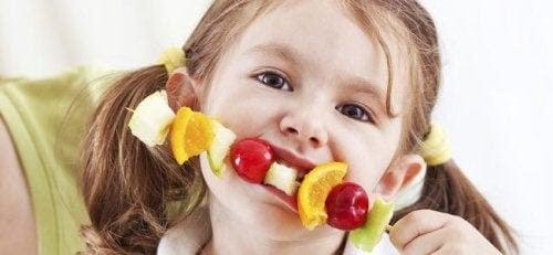 frukt tilltalande för barn: flicka äter frukt på spett