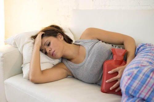 missar din mens: kvinna på soffa med varmvattenflaska för magen