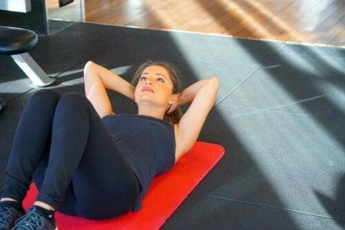 Kvinna gör situps under graviditeten