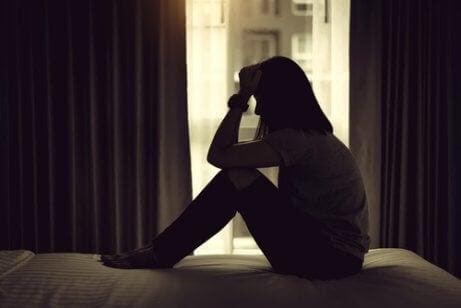 depression påverkar förhållandet: kvinna sitter på golvet i mörkt rum