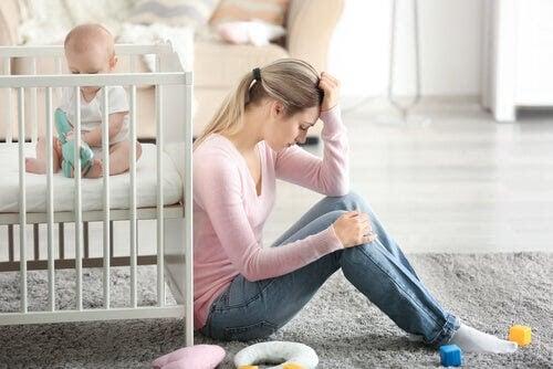 depression påverkar förhållandet: kvinna sitter på golvet bredvid spjälsäng