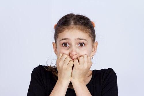 flicka känner skam och håller sig för munnen