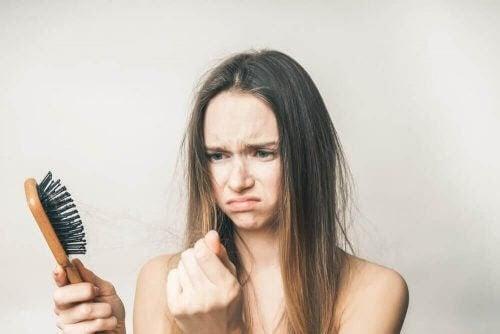 håravfall under graviditeten: kvinna med hårborste