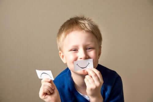 socio-emotionella förmågor: pojke med lappar med glad och ledsen mun