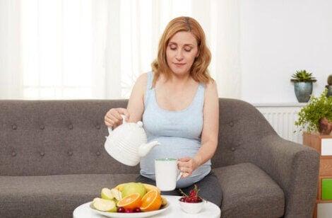 Halsbränna och matsmältningsbesvär under graviditeten: gravid kvinna häller upp te
