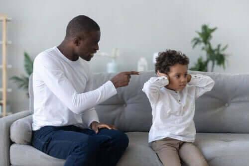 pappa skäller på son som håller för öronen