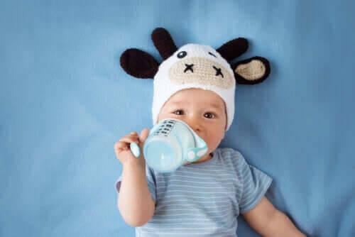 besök med din bebis: baby i söt mössa och med nappflaska