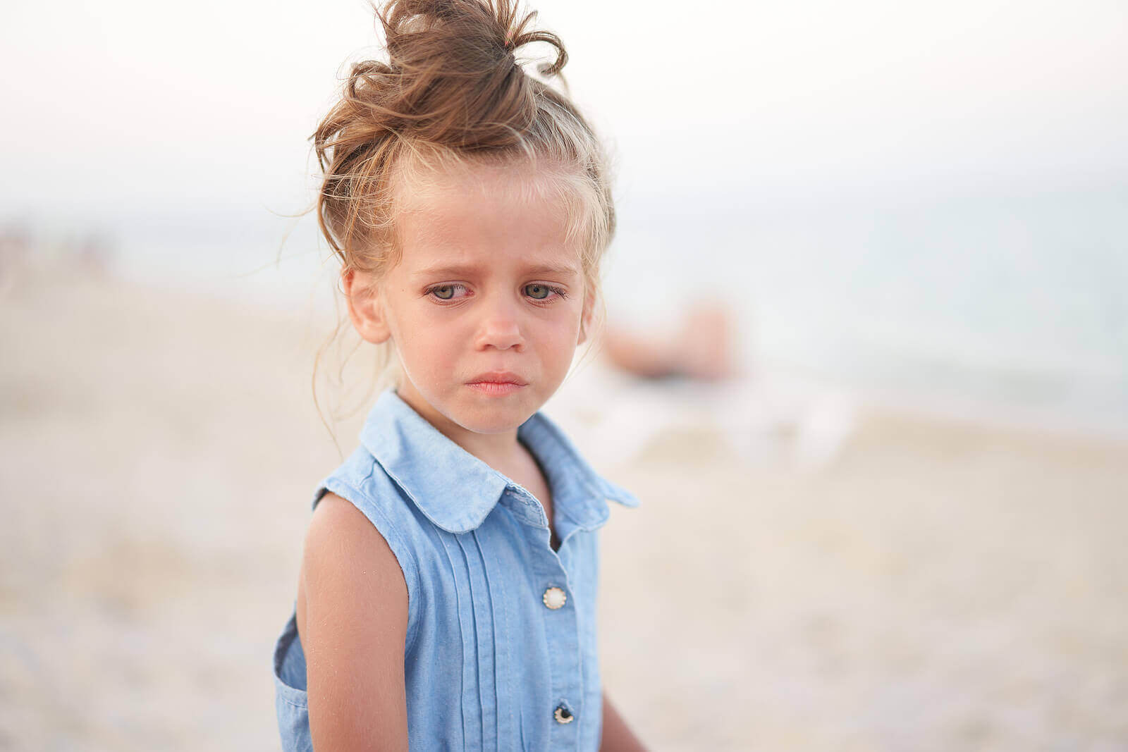 ett barn är ledset på strand