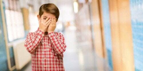 skadlig skam: pojke döljer ansiktet i händerna