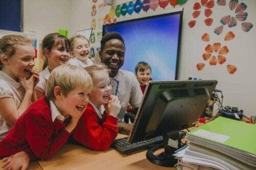lärare och elever framför dator