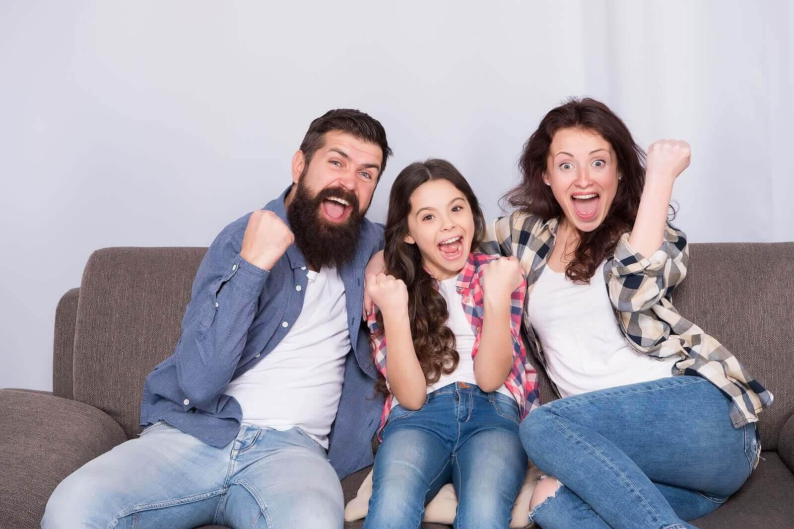 språklig kompetens hemma: glad familj i soffa