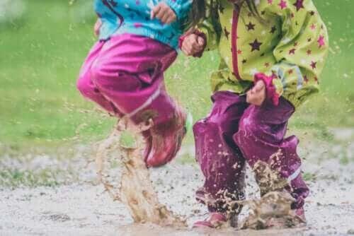 barn som hoppar i vattenpöl