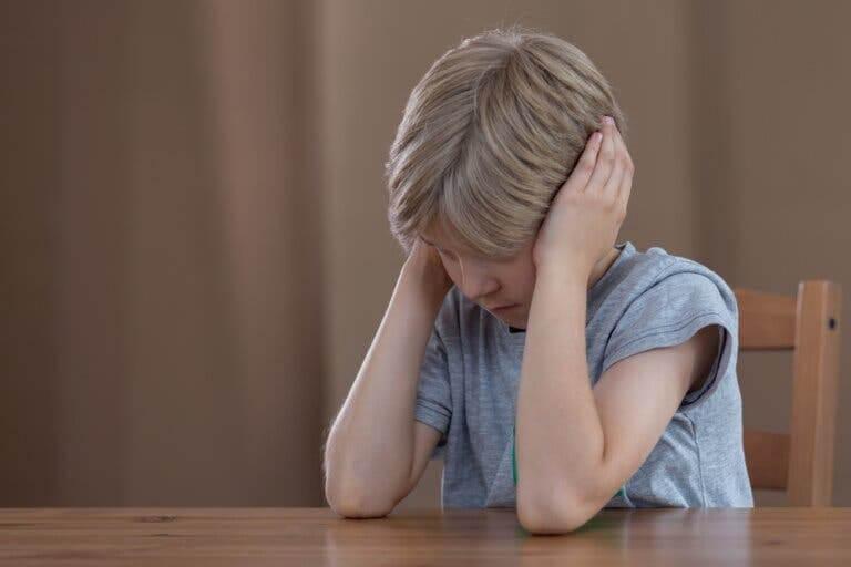 disciplinstrategier för högkänsliga barn: pojke sitter och håller sig för öronen