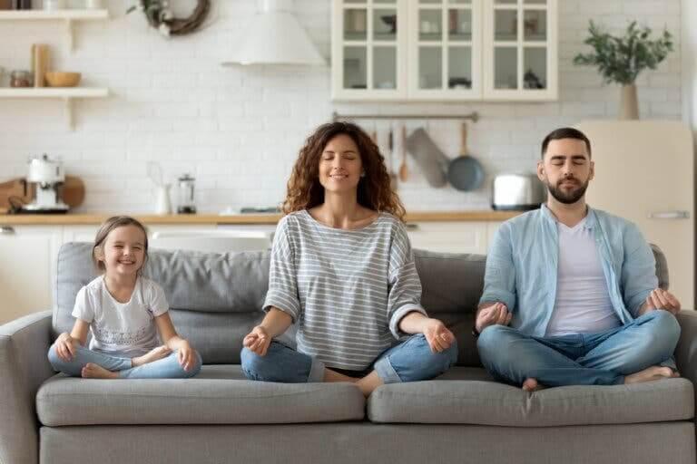 Mindfulness och meditation: familj mediterar i soffa