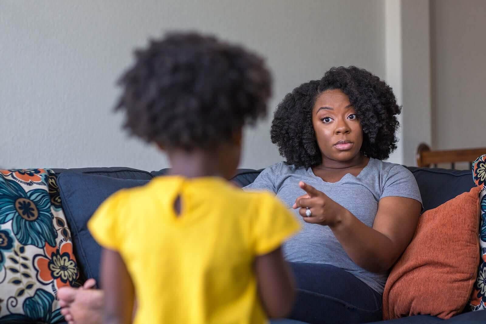 Disciplinära problem hos barn: mamma pekar på flicka