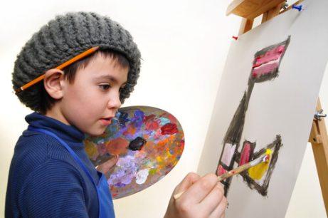 Hobbys för barn: En pojke som målar en tavla.