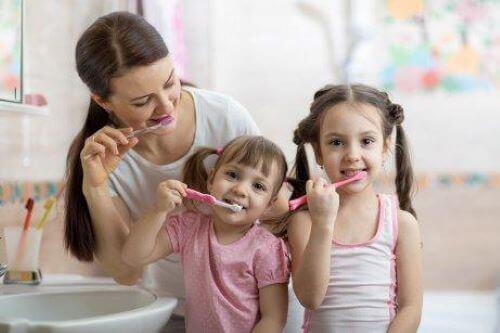 Familj borstar tänder tillsammans.