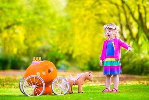 leka i trädgården: flicka med vagn av pumpor