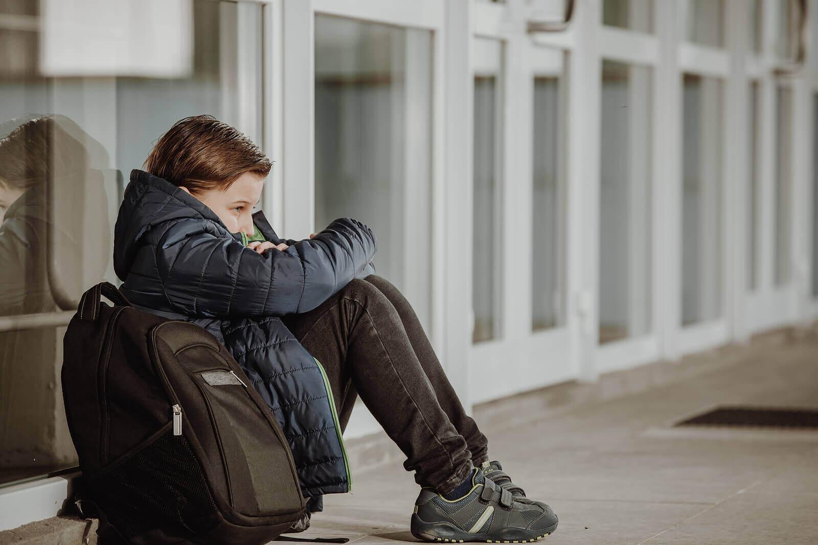 pennalism och kamratförtryck: nedstämd flicka sitter på marken