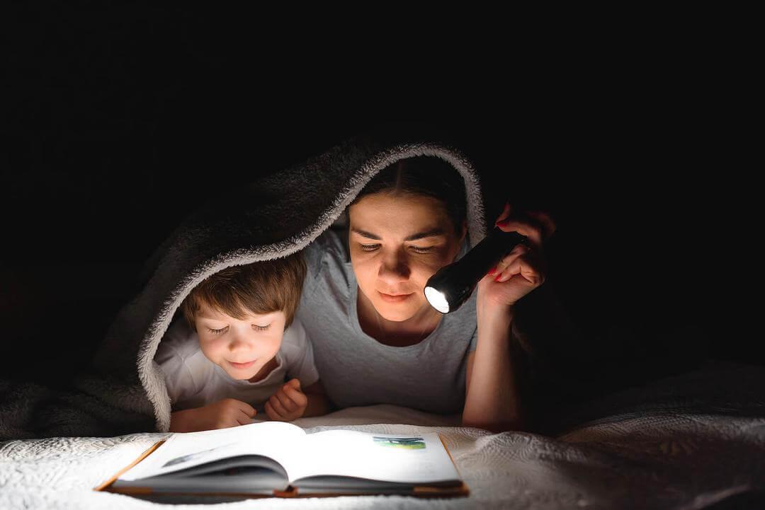 uppmuntra barn att läsa och skriva: mamma och barn läser under filt med ficklampa