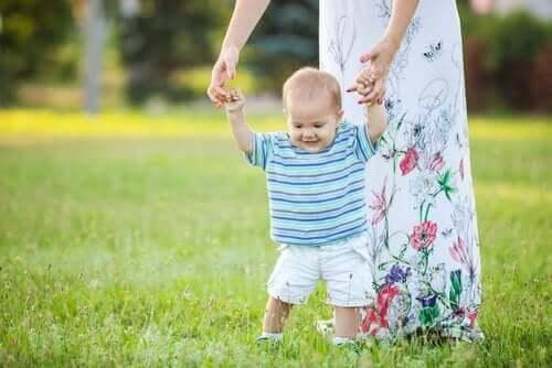 Benfrakturer hos småbarn: mamma hjälper baby gå på äng