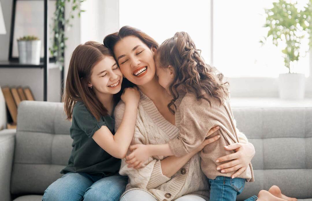 fysisk kontakt för barn: mamma och döttrar kramas i soffa