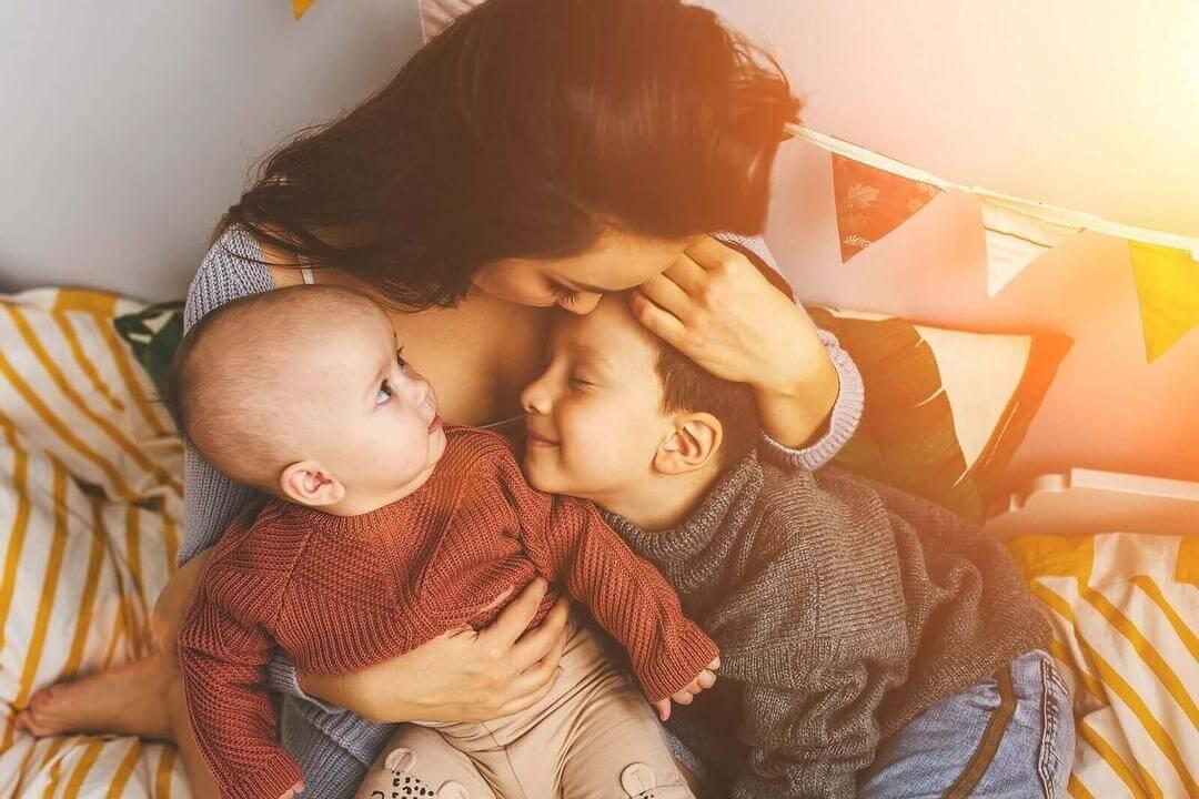 lyckliga föräldrar: mamma gosar med baby och barn