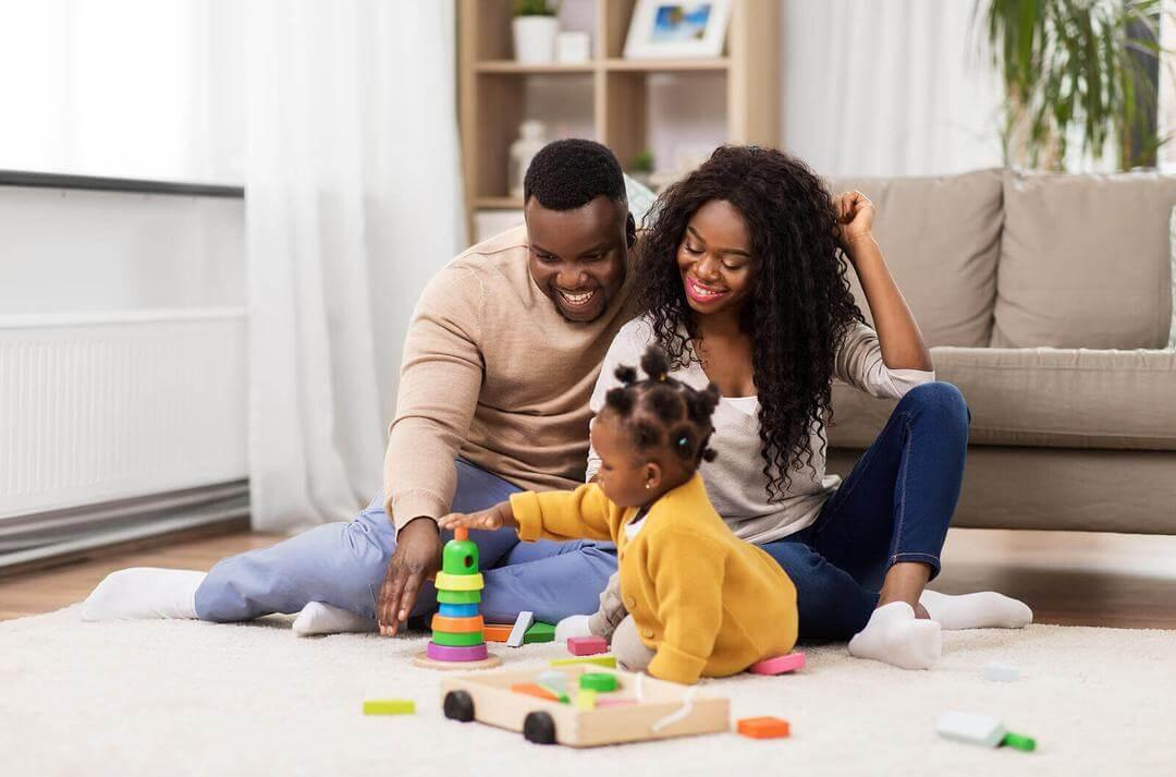 lyckliga föräldrar leker med klossar med baby