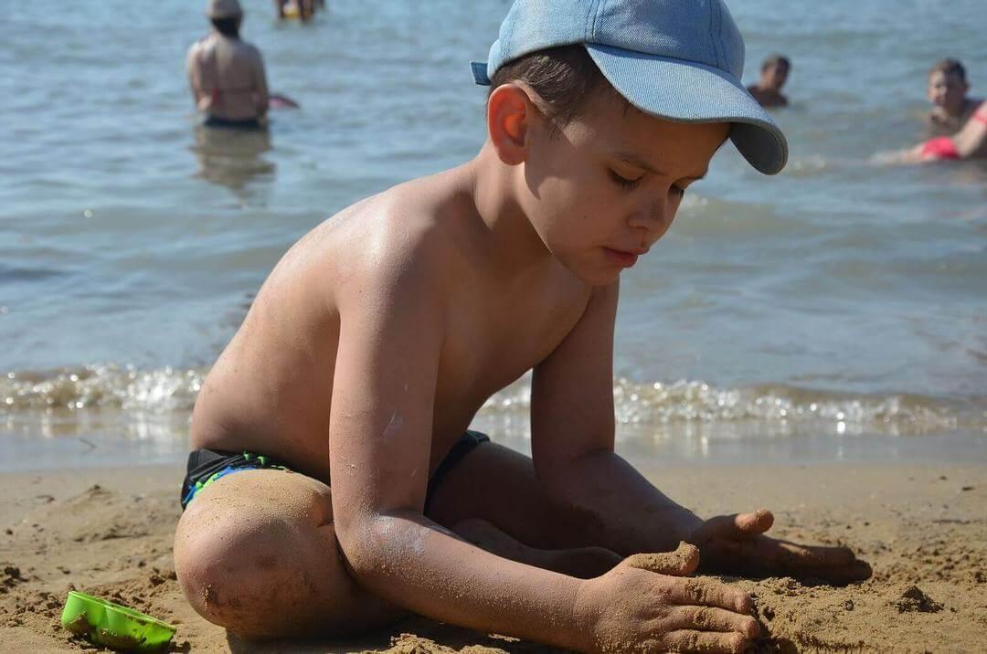 göra vid drunkning: barn bygger sandslott på stranden