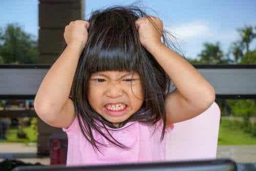 Barn drar sig i håret av frustration.